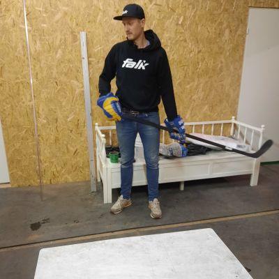 mies seisoo ja pitää käsissään kompositista tehtyä jääkiekkomailaa