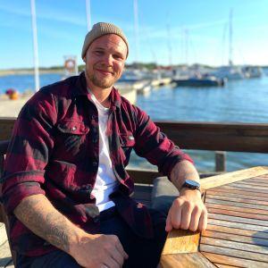 Jääkiekkoilija Taavi Vartiainen istuu ulkona pöydän ääressä satamassa.