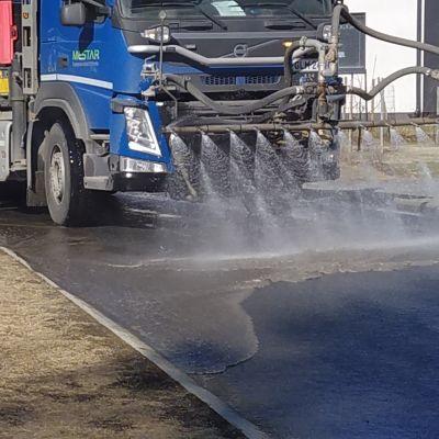 Tankkiauto pesee kadusta talven hiekoituspölyä