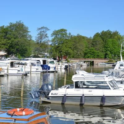 Båtar står förtöjda vid två kajar runt en å.