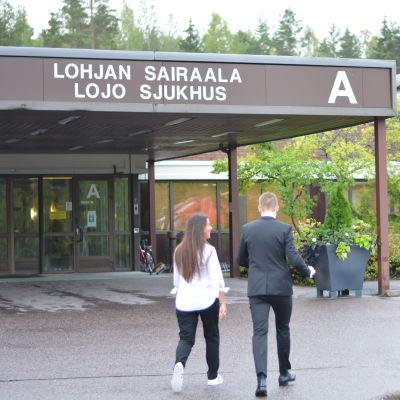 Två personer går in via huvudingången till Lojo sjukhus
