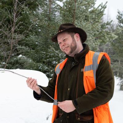 En man i jägarutryrsel håller i en trädgren av ett tunt träd som knäckts av på mitten.