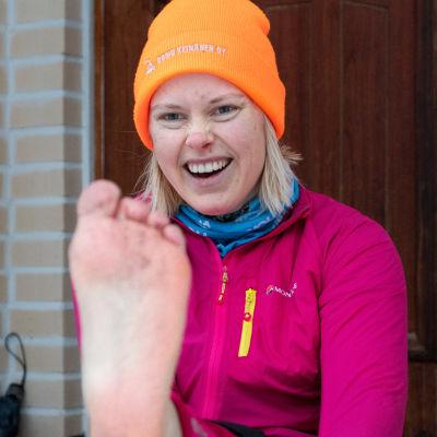 En kvinna i vinterkläder sträcker fram sin bara fot och ser ivrig ut.