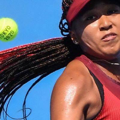 Närbild på Naomi Osaka med en tennisboll i närheten av huvudet.