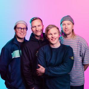 Kesäkumibändi Gasellit puoliksi vaaleanpunaisen, puoliksi sinisen seinän edessä. Artistit eli neljä miestä katsoo hymyillen kameraan.