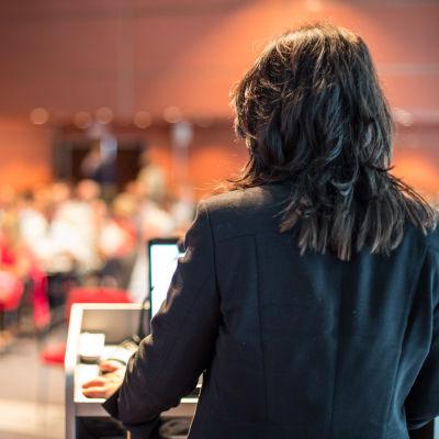 En kvinna föreläser i en sal.