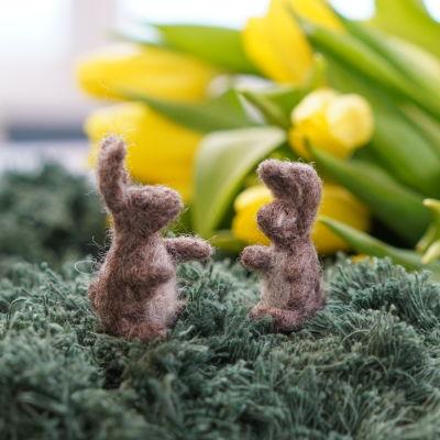 Två nåltovade miniatyrkaniner eller påskharar sitter på gräskulle gjord av garn.