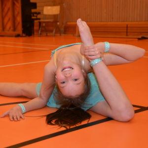 En flicka i turkos, glittrig dansdräkt. Hon heter Corinna Jälkö och är tävlingsdansare.