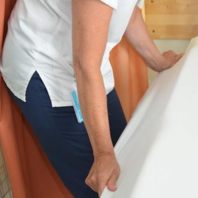 En vårdare bäddar en säng på en bäddavdelning.