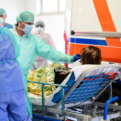 Läkare och sjukskötare runt tar hand om en patient som ligger i en säng bredvid en ambulans.