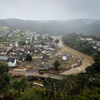 Joki ja kylä, jossa tuhoutuneita rakennuksia.