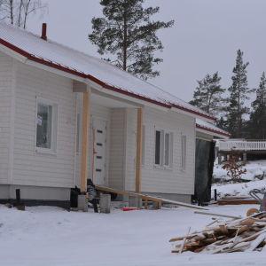 ett halvfärdigt hus, husbygge på gång. Vinter och snö. En hög med bräden. I bakgrunden ett färdigt, nybyggt hus.
