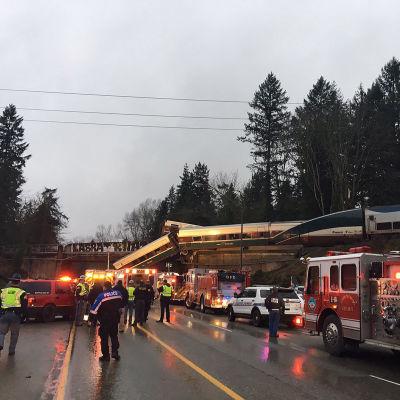 En tågvagn hänger från bron som går över motorvägen.