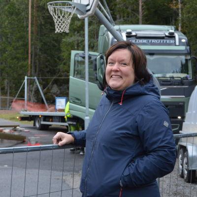 Vit kvinna med brunt hår står framför en barack som byggs.