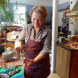 En kvinna dekormålar enchokladbit, en pralin i ett vanligt kök (hemma).