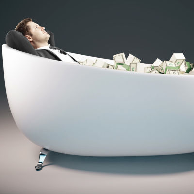 Rikas makaa rahaa täynnä olevassa kylpyammeessa.