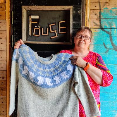 En kvinna håller upp en stickad tröja framför en dörr.