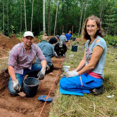 En man och en kvinna sitter vid ett sanddike vid en arkeologisk utgrävning.