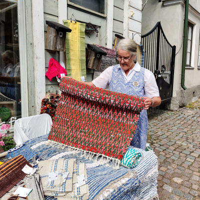 En kvinna står och håller upp en röd trasmatta utanför en affär.