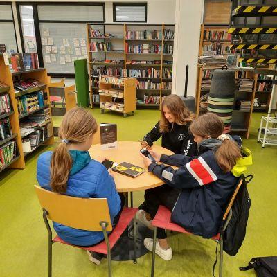Tre ungdomar sitter vid ett runt bord i ett bibliotek. Allihopa har mobiler i handen och tittar ner i mobilerna.