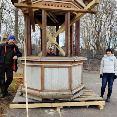 Ett torn av trä och tre personer som står runt tornet.