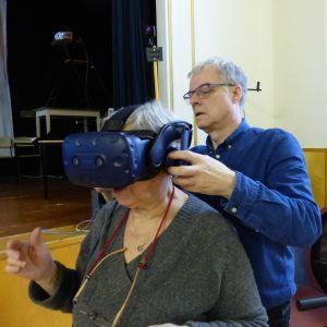 En kvinna sitter i en stol medan en man klär på henne ett par VR-glasögon.