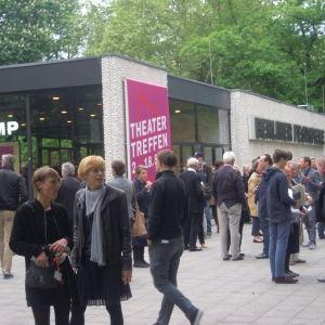 Theatertreffens hemmascen finns i Berlins Festspelhus. I publikvimlet inför ännu en föreställning råkar Theatertreffen-chefen Yvonne Büdenhölzer fastna på bild, hon står längst fram till höger.
