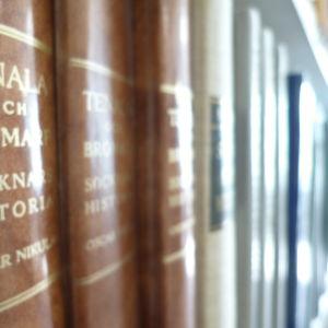 En bokrygg i brunt läder med gyllene bokstäver, Tenala och Bromarf socknars historia av Oscar Nicula. Tre bruna böcker i en bokrad på en bokhylla.
