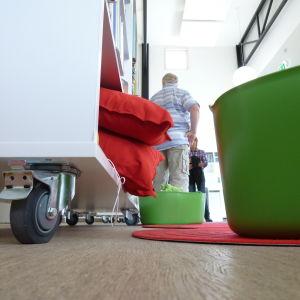 En vit bokhylla med hjul under, röda sittdynor syns på nedersta hyllan, en grön balja för saker och böcker, i bakgrunden står mänskor. Grodperspektiv.