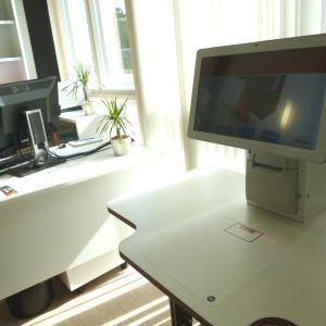 En låneautomat, en dator som man visar biblioteksbokens streckkod för för att låna den. I bakgrunden ett arbetsbord med vanlig bokdator. Solen lyser in i rummet. Bibliotek.