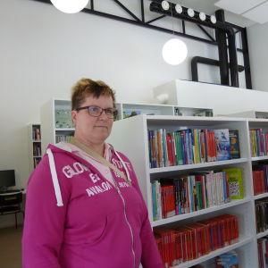 En kvinna i pink munktröja står framför ljusa bokhyllor.