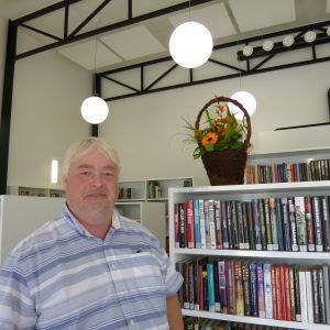 En gråhårig glad man i sommarskjorta står framför bokhyllor. På en hylla står en blomsterkorg med orangefärgade blommor.