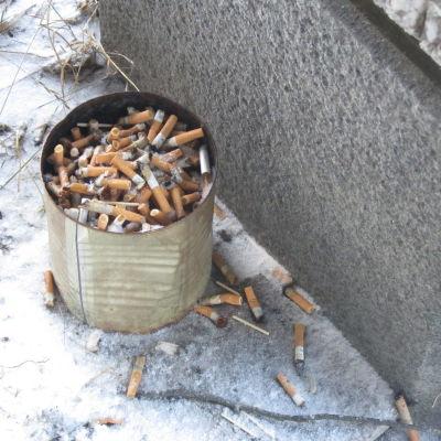 En stor konservburk full med tobaksfimpar står vid en vägg. På marken syns snö, fimpar och tändstickor.