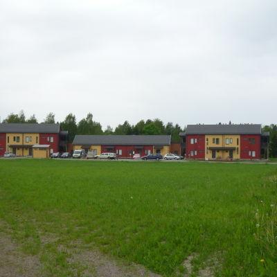 Tre rödgula hus med träfasad, en grön gräsplan i förgrunden.