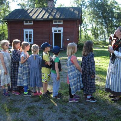 Barn på traditionsläger på Brage Friluftsmuseum tillsammans med guide Jenny Holm