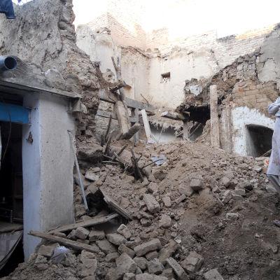 En pojke i Kohat i Pakistan tittar på sitt förstörda hem.