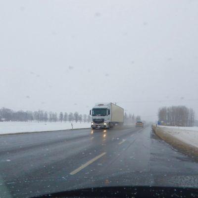 Lastbil kör i dåligt före i snöslaskväder.