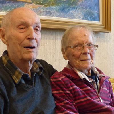 Eric och Helena Lindqvist sitter bredvid varandra i soffan. Eric håller sin arm om Helena