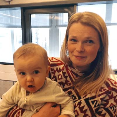 Porträttfoto av Linn Holmgård med bebis i famn.