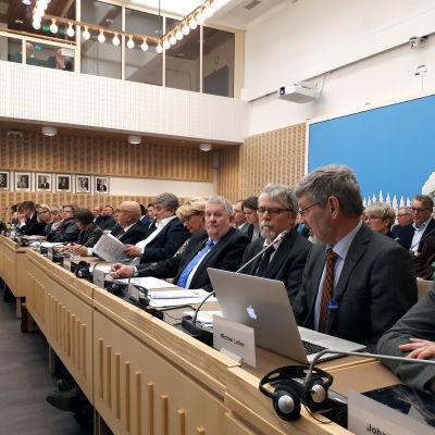 Fullmäktigeledamöter på rad fullmäktigesalen i Korsholm