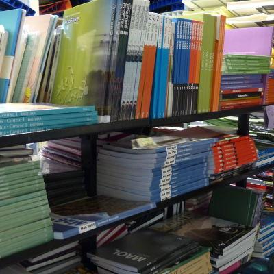 Många skolböcker (gymnasieböcker) på hyllor i en bokhandel.