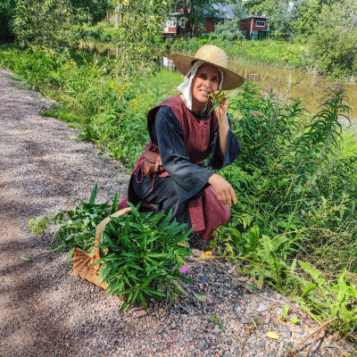 En kvinna sitter på huk bredvid en vägren och äter på en växt.