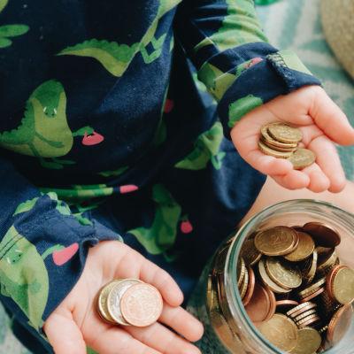 Ett barn håller mynt i båda händerna bredvid en glasburk full av mynt.