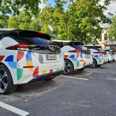 Flera vita bilar med färgglada dekorationer parkerade bredvid varandra.