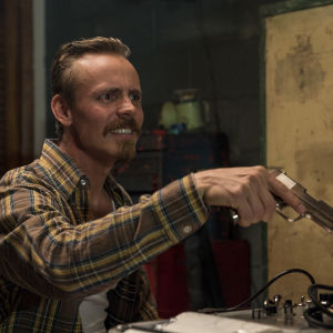 Felix (Jasper Pääkkönen) ser arg ut och viftar med en pistol.