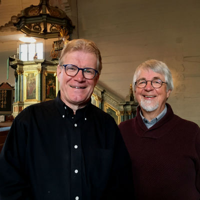 Lars-Johan Sandvik och Johan Klingenberg ser glada in i kameran, i bakgrunden predikstolen i Nykarleby kyrka.