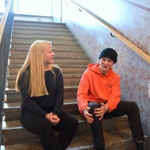 Högstadieeleverna Saga Portman och Matias Wentzel sitter i en av skolans trappor och pratar.