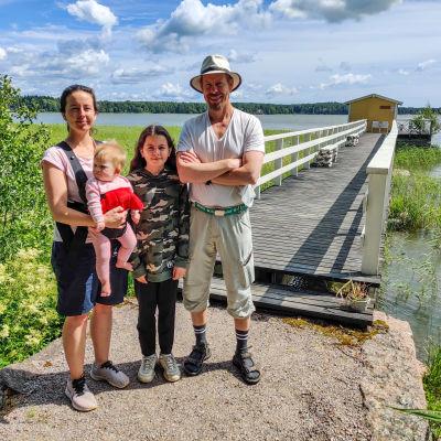 En kvinna och en man med två barn står på en brygga framför vattnet.
