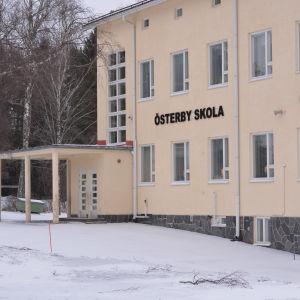 En skolbyggnad i flera våningar byggd i ljusmålad betong. Det står Österby skola på fasaden. På väggen finns också en stor, rund klocka. Vinter och snö, inga skolbarn.