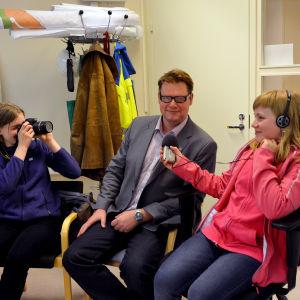 Kaia Paukku och Alicia Äbb från Ekenäs högstadieskola intervjuar och fotar tekniska direktören i Raseborg, Jan Gröndahl.